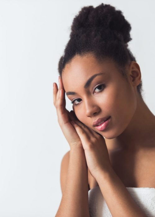 Beautiful Afro-American girl in towel is touching her face and looking at camera, isolated on white